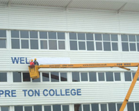 Two workers in the basket of Cherry Picker applying a sign to the front of Preston College
