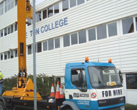 Cherry Picker parked outside of Preston College as workers use the basket to apply the sign