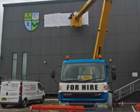 Cherry Picker used to apply a logo to the side of a building