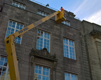 Worker using a Cherry Picker to work on the top of a tall building