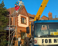 Man using Cherry Picker to install Christmas decorations on the roof of a home